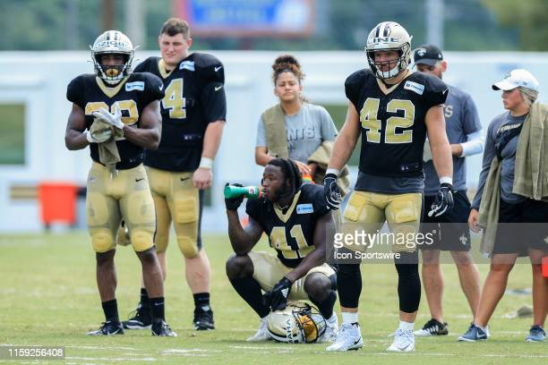 New Orleans Saints running back Alvin Kamara hydrates as fullback Zach Line looks on during training camp on August 2 2019 at the Ochsner Sports...