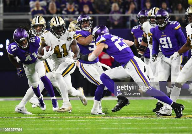 New Orleans Saints Running Back Alvin Kamara runs with the ball as Minnesota Vikings Safety Anthony Harris and Minnesota Vikings Safety Harrison...