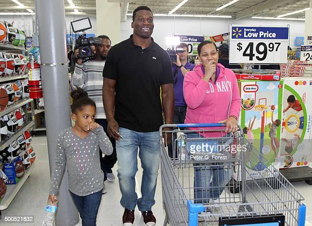 New Orleans Saints tight end Benjamin Watson and his sixyear old daughter Grace both walk with a shopper at Walmart Supercenter on December 8 2015 in...