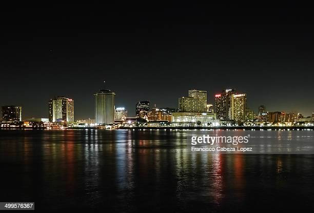 CONTENT] New Orleans skyline illuminated at night and reflected on Mississippi river Downtown business district skyscrapers at night