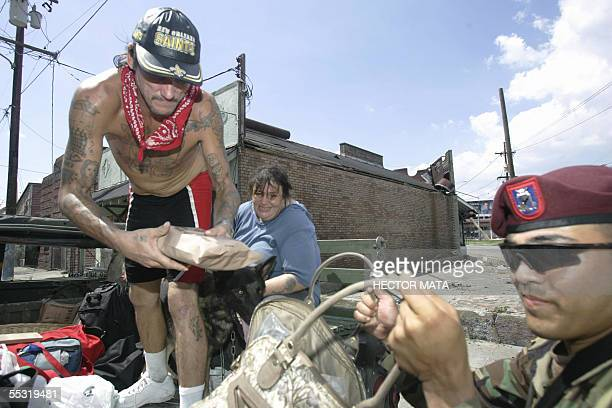 New Orleans, UNITED STATES: A man leaves his house escorted by members of the 82nd Airborne Division 08 September 2005 in the French Quarter of New...