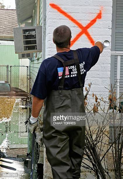 A member of the Los Angeles County Fire Departament marks a house in a flooded sector of New Orleans 12 September 2005 US soldiers police and firemen...