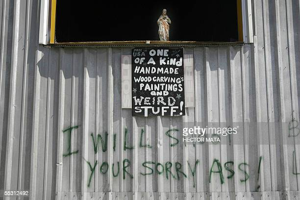 A sign is scrawled beneath a statue of Jesus Christ as a warning to looters 07 September 2005 in New Orleans Some one million residents have been...
