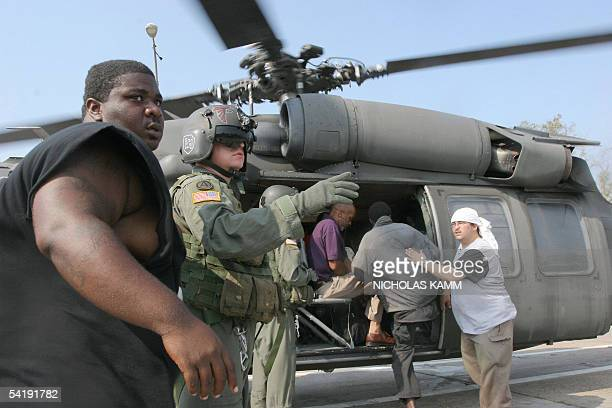 A US army soldier and a New Orleans sheriff direct stranded people to board a helicopter on an overpass near the Superdome in New Orleans 02...