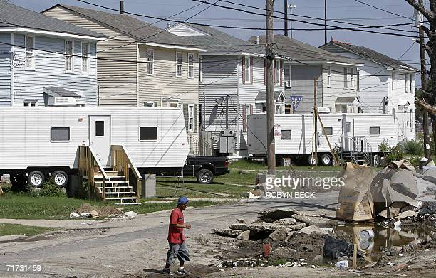 A worker crosses a street lined with FEMA trailers and flooddamaged homes still under repair in the Gentilly section of New Orleans 28 August 2006...