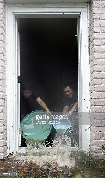 Cuong Pham and Bich Tran who are PhD students at Tulane University in New Orleans Louisiana bail water from their basement apartment in the Garden...
