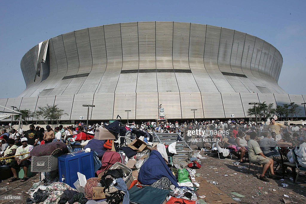 Hurricane Katrina survivors wait outside the Superdome and Convetion Center in New Orleans 02 September, 2005. The New Orleans sports arena that housed hurricane refugees for five days in lawless squalor was finally emptied Friday, though many remained stranded with no immediate prospect of evacuation. While relieved to leave the confines of the Superdome, where many testified to pitch-dark nights of gunfire, rioting and rape, the evacuees found the devastated city outside offered little in the way of comfort.