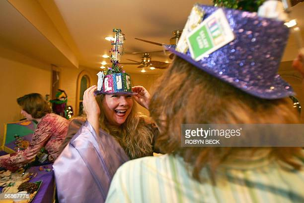 Members of the allwomen Muses Mardi Gras krewe or team Trudi Ruppenicker and Donna Reeve try on their parade hats at a float party and meeting at the...