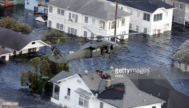 New Orleans, UNITED STATES: Residents are rescued by helicopter from the floodwaters of Hurricane Katrina 01 September 2005 in New Orleans,...