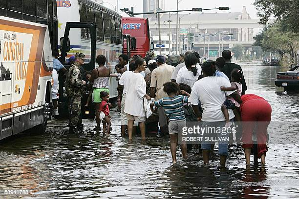 Soldiers watch people boarding buses near the Superdome in New Orleans 01 September as they begin leaving the arena to be brought to the Astrodome in...