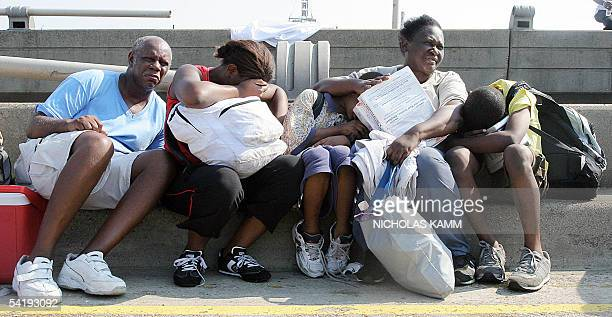 Stranded people wait to be airlifted by a US army helicopter from an overpass near the Superdome in New Orleans 02 September as evacuations finally...