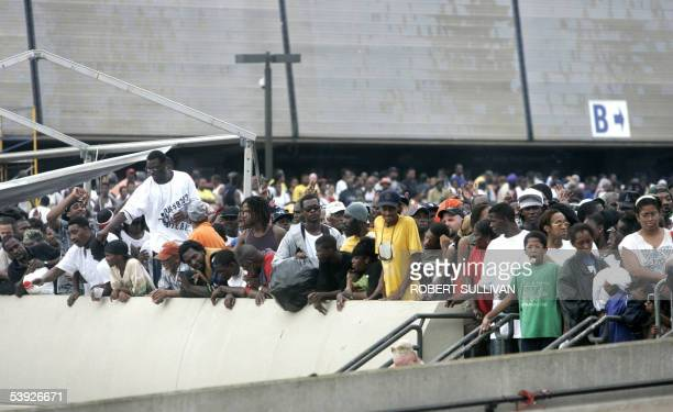 Thousands of people stand outside the Superdome in New Orleans 01 September 2005 as they wait to be walked out to busses which will bring them to the...