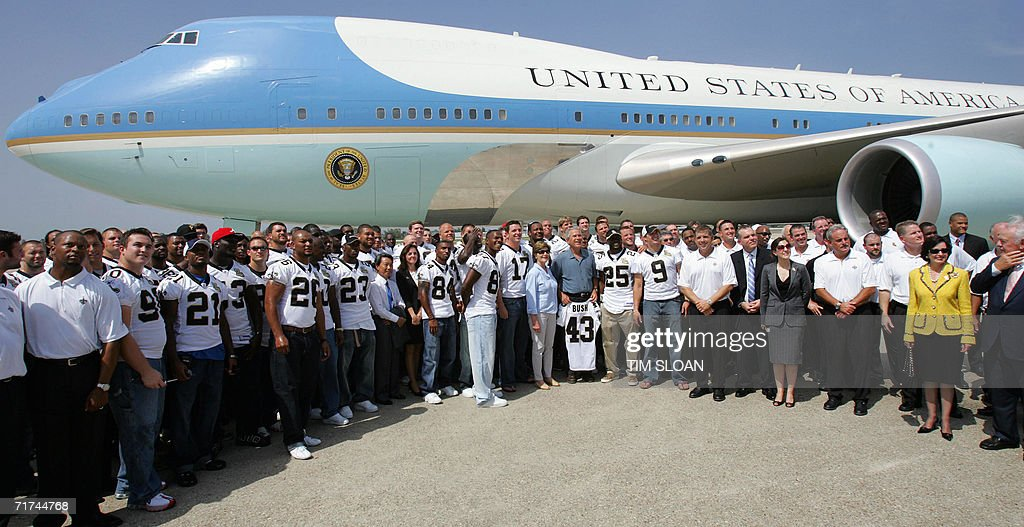 US President George W. Bush and First Lady Laura Bush (C) pose for photos with the New Orleans Saints National Football League team at Louis Armstrong International Airport 29 August 2006 in New Orleans, Louisiana. One years after Hurricane Katrina devastated New Orleans, Bush mourned Katrina's victims and promised to do right by its survivors.