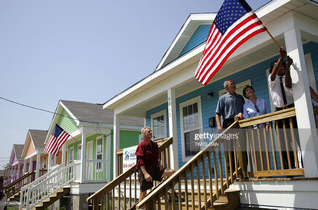 US President George W. Bush and First Lady Laura Bush watch as musician J.D. Hill (R) hangs an American flag outside his new home built by Habitat For Humanity in the Lower Ninth Ward 29 August 2006 in New Orleans, Louisiana. On the first anniversary of Hurricane Katrina, Bush took 'full responsibility' for Washington's botched response to the disaster, promised 'we're addressing what went wrong' and predicted that this festive city would someday be 'louder, brasher and better.'