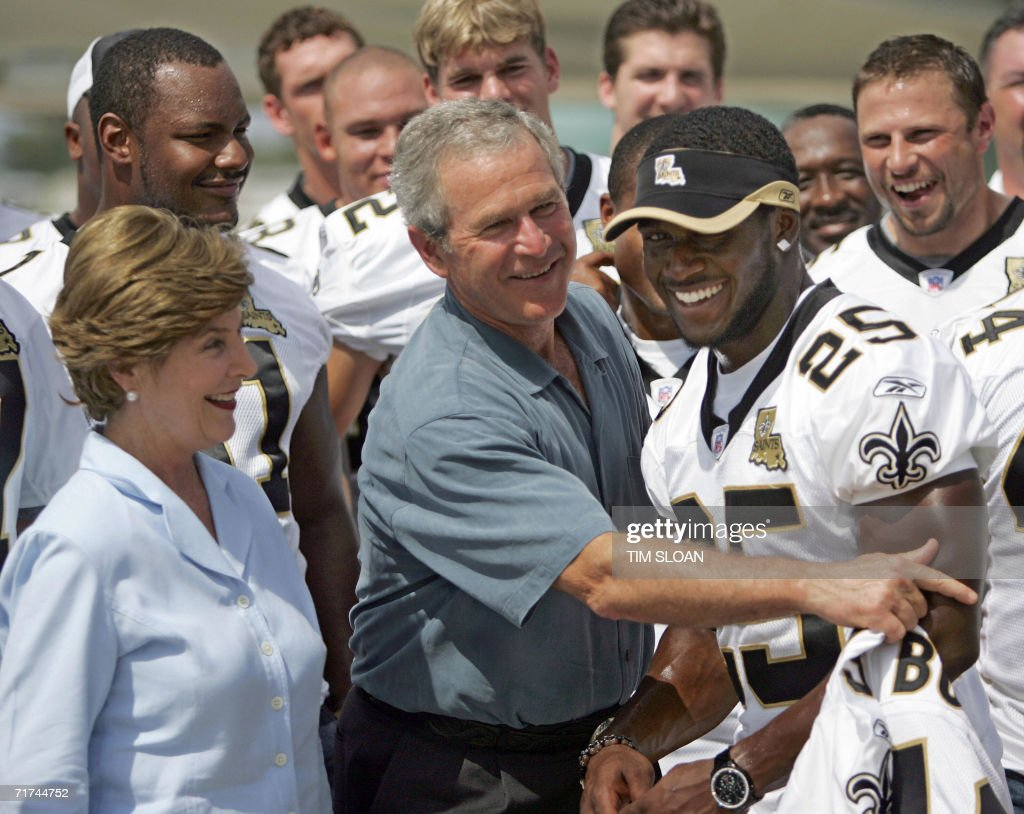 US President George W. Bush (C) jokes with New Orleans Saints player Reggie Bush (R) beside US First Lady Laura Bush (L) at Louis Armstrong International Airport 29 August 2006 in New Orleans, Louisiana. One year after Hurricane Katrina devastated New Orleans, Bush mourned Hurricane Katrina's victims and promised to do right by its survivors.