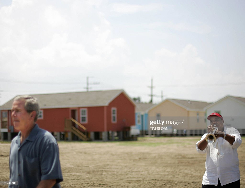 US President George W. Bush walks by a trumpet player from the New Birth Brass Band while touring a Habitat For Humanity site in the Lower Ninth Ward 29 August 2006 in New Orleans, Louisiana. Bush took 'full responsibility' for Washington's botched response to the disaster, promised 'we're addressing what went wrong' and predicted that this festive city would someday be 'louder, brasher and better.'