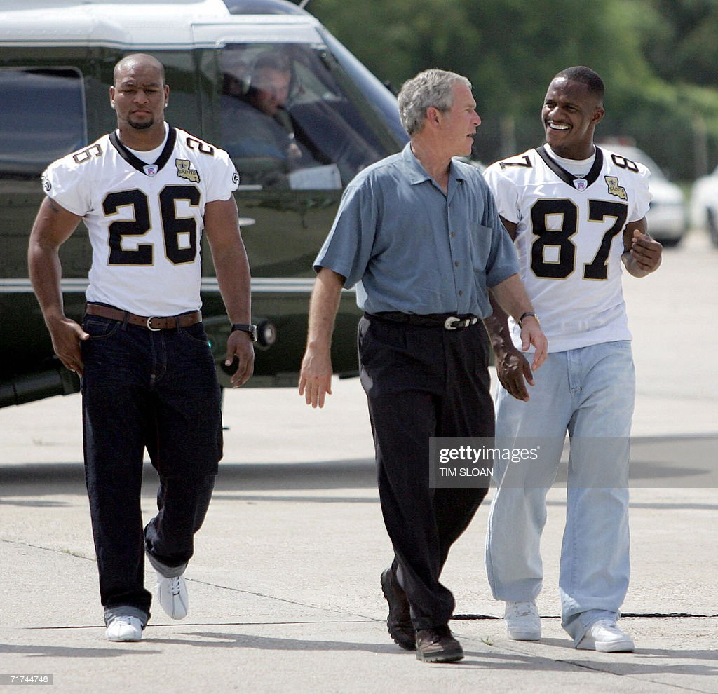 US President George W. Bush (C) walks with New Orleans Saints players Joe Horn (R) and Deuce Mcallister (L) after arriving aboard Marine One at Louis Armstrong International Airport 29 August 2006 in New Orleans, Louisiana. One year after Hurricane Katrina devastated New Orleans, Bush mourned Hurricane Katrina's victims and promised to do right by its survivors.