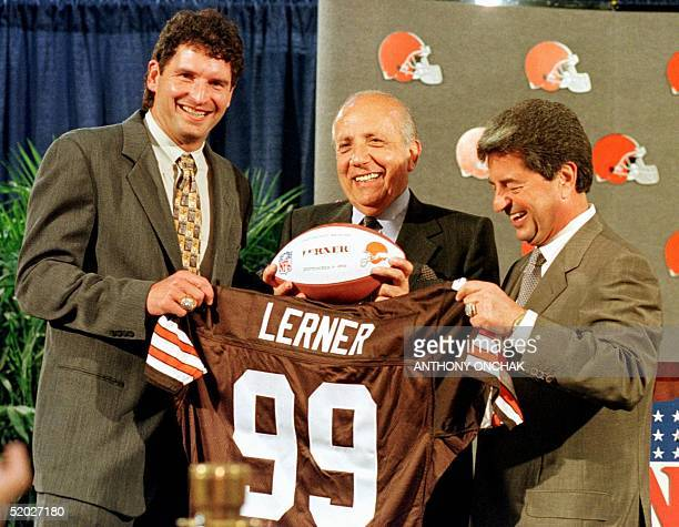 New owner of the Cleveland Browns Alfred Lerner Carmen Policy and former Cleveland Browns quarterback Bernie Kosar hold up a team jersey and football...