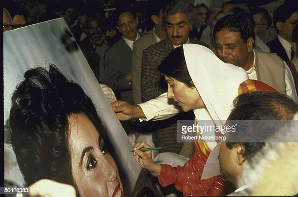 New Pakistani Prime Minister Benazir Bhutto autographing a portrait of herself after her election.