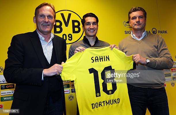 New player Nuri Sahin poses with chairman Hans Joachim Watzke and manager Michael Zorc during a Borussia Dortmund press conference at Signal Iduna...