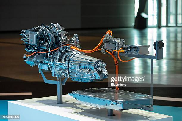 A new pluginhybrid engine and powertrain system sit connected to a battery during Daimler AG's TecDay Road to the Future event in Stuttgart Germany...