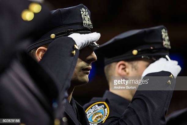 New police recruits salute during the New York Police Department graduation ceremony on December 29 2015 at Madison Square Garden in New York City...