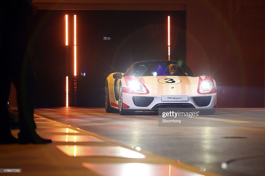 A new Porsche 918 Spyder automobile, produced by Porsche SE, is driven on stage during a news conference ahead of the opening day of the 84th Geneva International Motor Show in Geneva, Switzerland, on Monday, March 3, 2014. The International Geneva Motor Show will run from Mar. 4, and showcase the latest models from the world's top automakers. Photographer: Chris Ratcliffe/Bloomberg via Getty Images