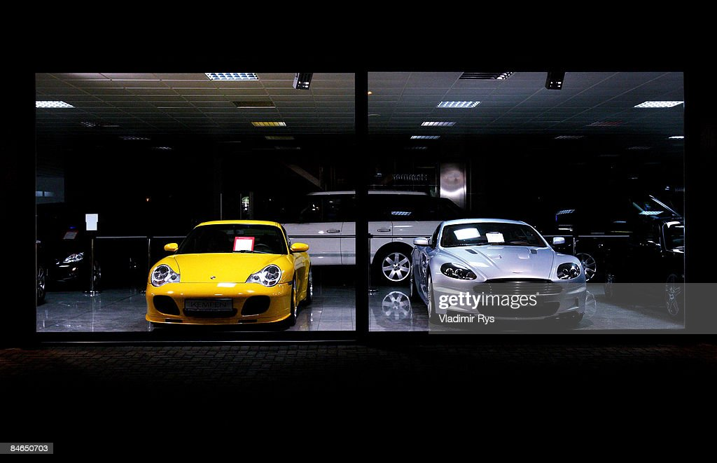 ed6f0e03fc A new Porsche and Aston Martin are parked in a car dealer showroom ...