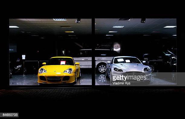 A new Porsche and Aston Martin are parked in a car dealer showroom on February 4 2009 in Cologne Germany Germany western Europe's largest auto market...