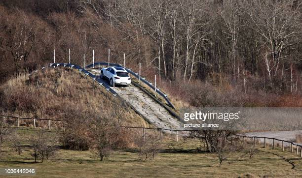 A new Porsche Macan drives along the offroad test track at the Porsche factory in Leipzig Germany 25 February 2014 Since the start of production on...