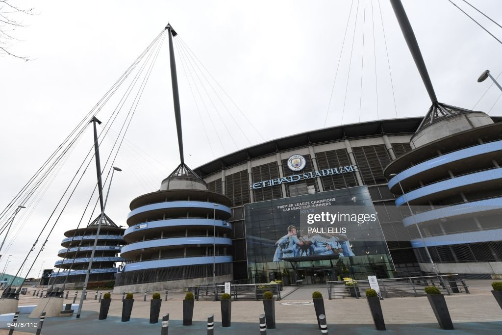 A new poster showing members of the Manchester City team celebrating has been placed at the entrance to the Etihad Stadium in Manchester, north west England to celebrate Manchester City winning the Premier League title on April 16, 2018. Pep Guardiola's side were crowned kings of English football yesterday as their arch rivals Manchester United slumped to a shock 1-0 defeat against struggling West Bromwich Albion. / AFP PHOTO / Paul ELLIS / RESTRICTED TO EDITORIAL USE. No use with unauthorized audio, video, data, fixture lists, club/league logos or 'live' services. Online in-match use limited to 75 images, no video emulation. No use in betting, games or single club/league/player publications. /