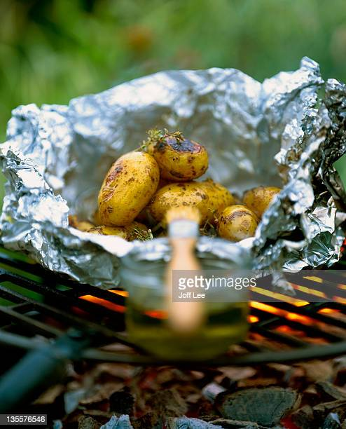 New potatoes wrapped in foil on barbecue