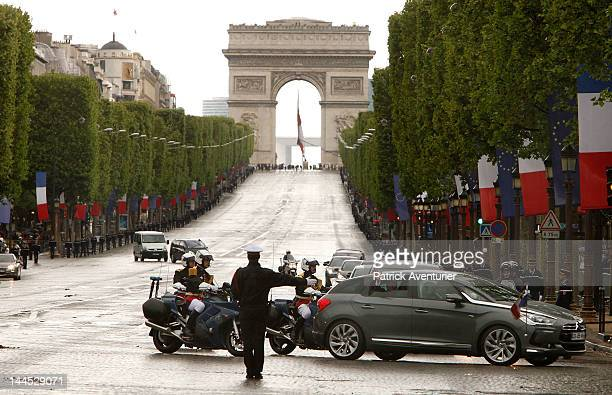 New President Francois Hollande waves from his car as he makes his way down the Champs Elysees avenue after the presidency handover ceremony on May...