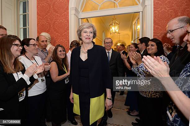 New Prime Minister Theresa May followed by her husband Philip John is welcomed by staff as she walks into 10 Downing Street after meeting Queen...
