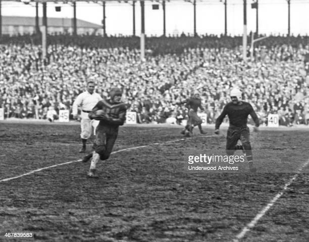 New pro football player Harold 'Red' Grange receiving a forward pass and making a 20 yard run New York New York December 6 1925 Grange made his NY...