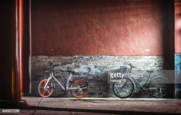 New public bicycle and an old personal one, parked by the Forbidden City Palace Museum at night