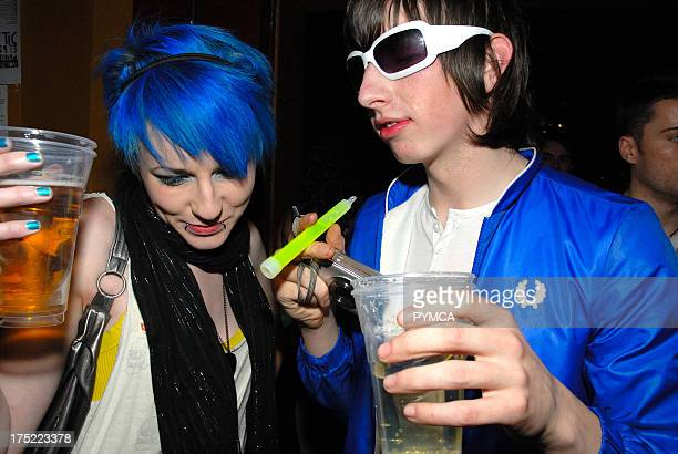 New rave couple girl with blue hair and boy in electric blue jacket holding a camera and a glowstick CSS gig February 2007