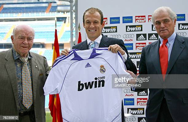 New Real Madrid football player Arjen Robben of the Netherlands stands with his jersey next to Honor President Alfredo Di Stefano and Real Madrid's...