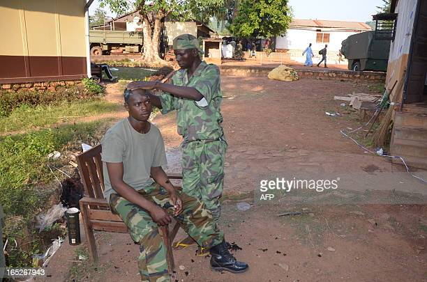 A new recruit of the Seleka rebel army has his hair cut in a military barracks in Bangui on April 2 2013 The Central African Republic's new postcoup...