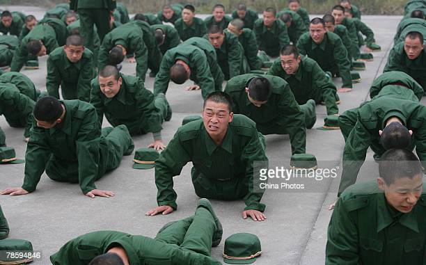 New recruits do pushups at a military training base on December 20 2007 in Chongqing Municipality China Recruits are required to undergo three to...