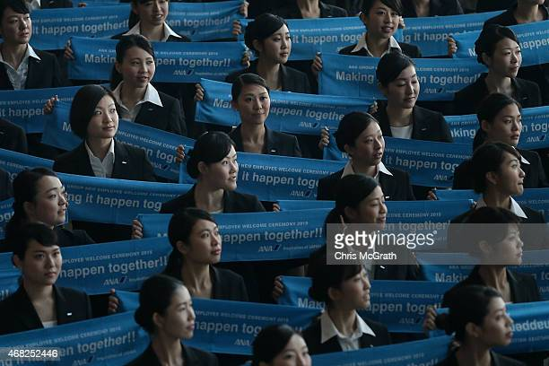 New recruits hold up banners for a group photograph during the welcome ceremony for new employees of All Nippon Airways Holdings at ANA hanger on...