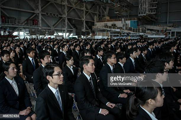 New recruits listen to speeches during the welcome ceremony for new employees of All Nippon Airways Holdings at ANA hanger on April 1 2015 in Tokyo...