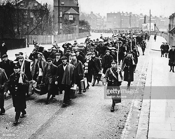 New recruits march alongside armed officers following the outbreak of the First World War.