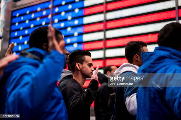 New recruits raise their hands as they take an oath outside the renovated Times Square Military Recruiting Station in New York on November 10 2017 ...