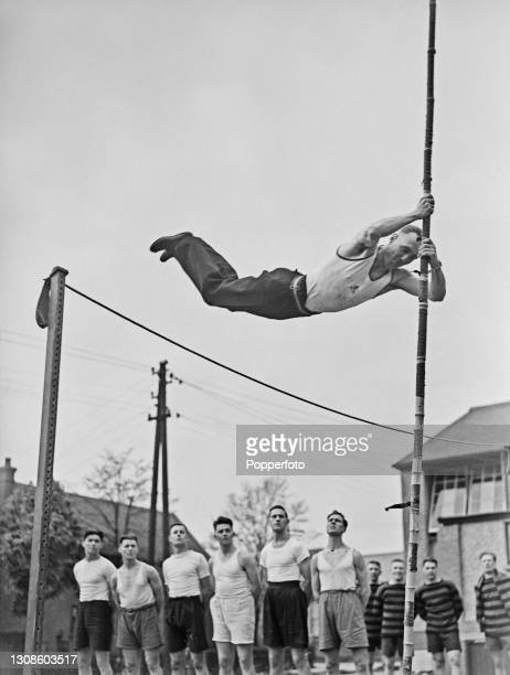 New recruits watch an instructor from the Royal Army Physical Training Corps complete a pole vault jump over a raised bar at a British Army barracks...