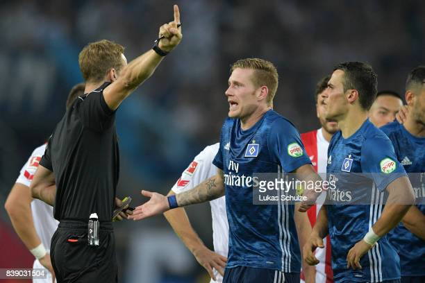 New referee Soeren Storks argues with Andre Hahn of Hamburg and Filip Kostic of Hamburg the Bundesliga match between 1 FC Koeln and Hamburger SV at...
