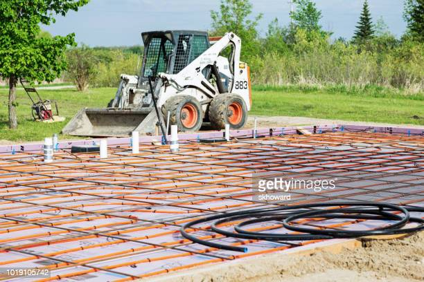 new residential concrete slab with radiant floor heating  -  preparation and equipment - bobcat stock pictures, royalty-free photos & images