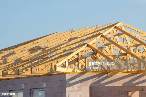 new residential construction home framing over blue sky - rebuilding stock pictures, royalty-free photos & images