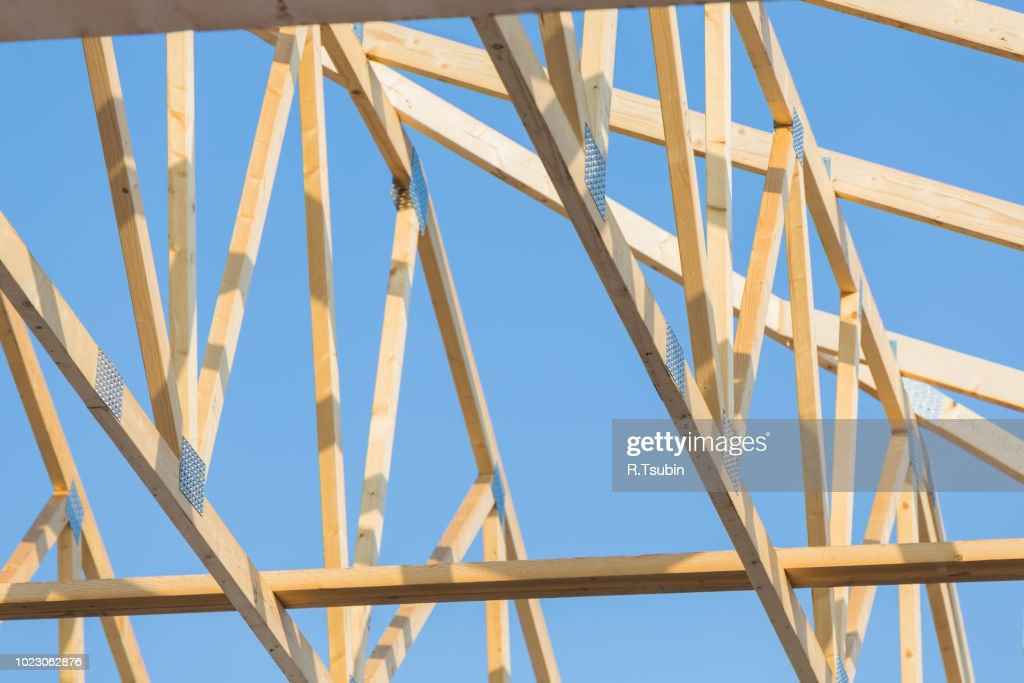 new residential construction roof home framing against a blue sky