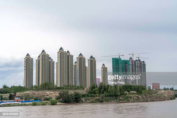 New residential houses are built along the Yellow river China's National Bureau of Statistics said that new home sales in China rose by 40% in the...